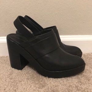 Intentionally blank black heeled mules